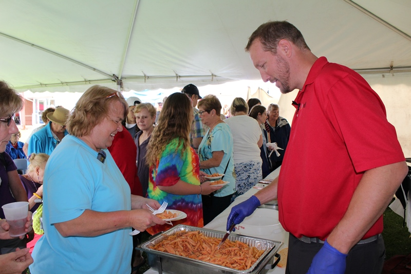 This photo shows a male serving food at the food festival
