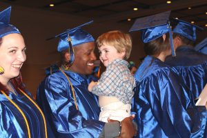 This photo shows a smiling male graduate holding a child