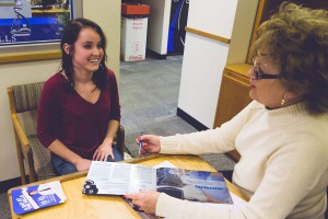 This photo shows a smiling student speaking with an admissions representative