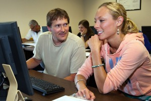 This photo shows a male and female student working collaboratively at a computer