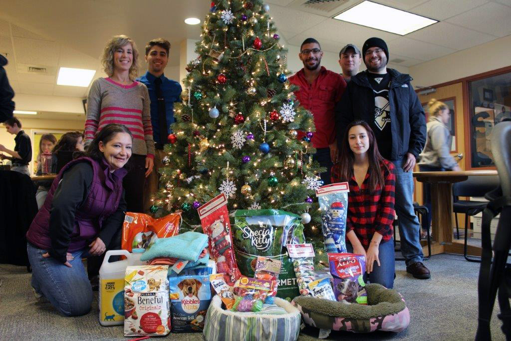 This photo shows students around a Christmas tree with donations