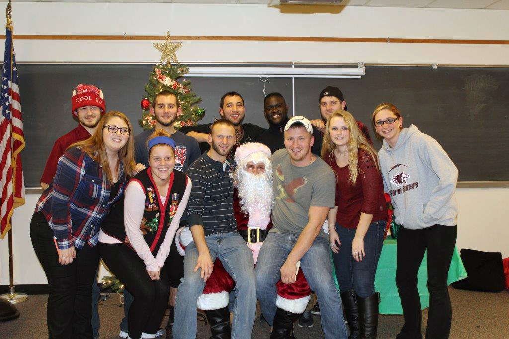 This photo shows a group of smiling students with Santa Claus
