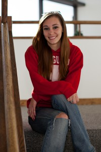 This photo shows a smiling female sitting on the stairs at the Altoona campus