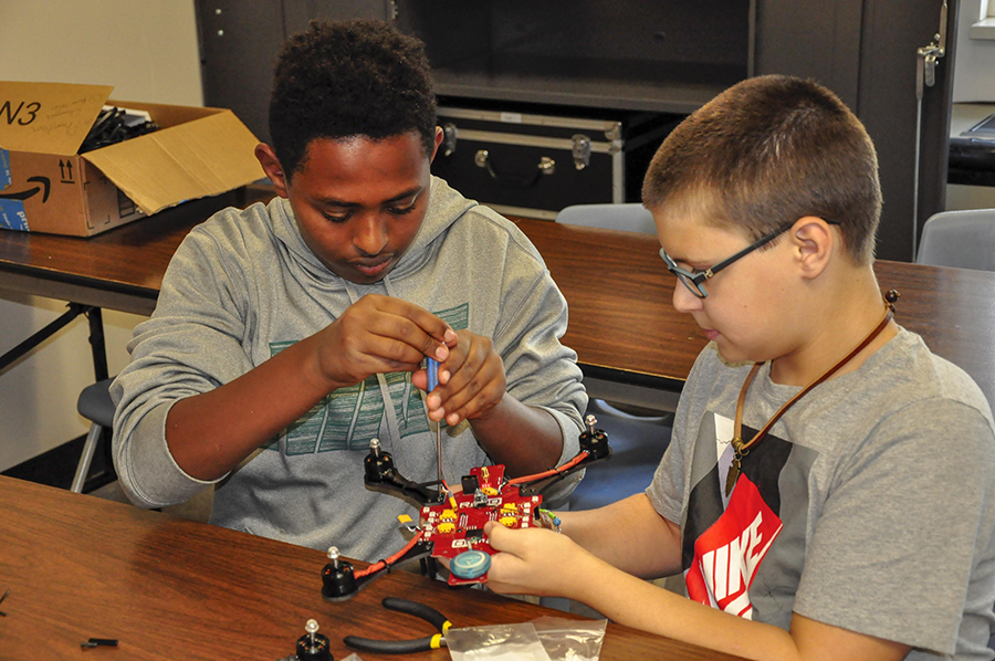 Two PA Cyber Charter Schools students are shown as they assemble a RubiQ racing drone.