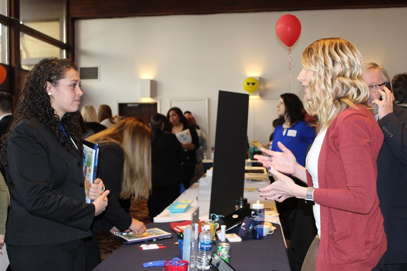 This photo shows a student speaking with a local employer at the career fair