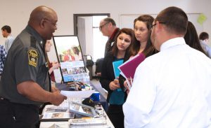 This photo shows students speaking to local employers the the career fair