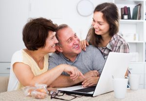 Two females and a male sitting around a computer smiling