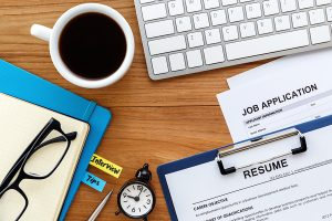 A still life image of a job application and resume