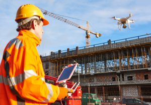 Male flying a drone over a construction site