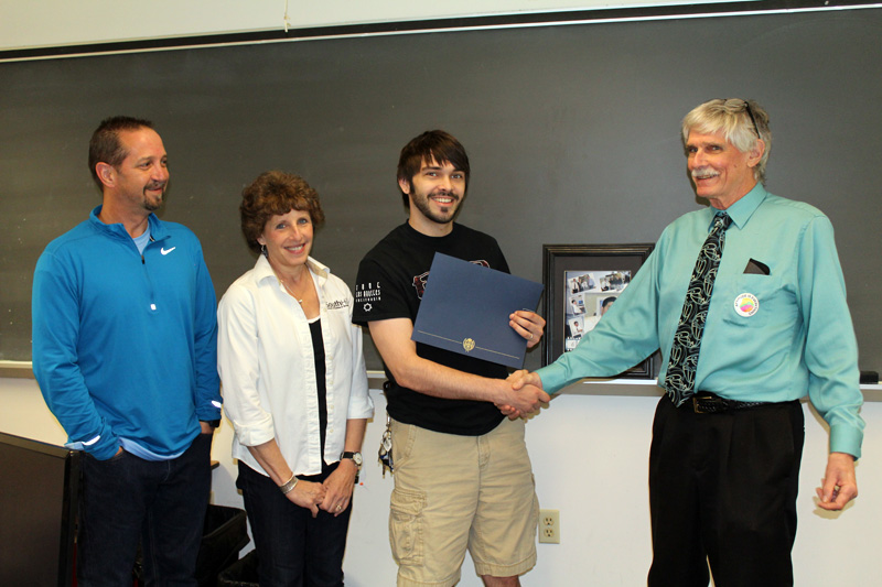 This photo shows a smiling student receiving an award from faculty members