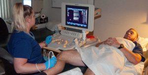 Sonographer examining veins in patient's leg