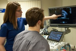 This photo shows two students using a sonography/ultrasound imaging machine.