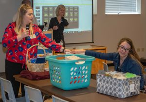 South Hills DMS 2019 class representative Lesley Hogan, left, holds the basket while DMS second-year class representative Robyn Pheasant draws the willing ticket for the 2019 basket raffle. DMS Program Director, Tricia Turner, watches in the background.