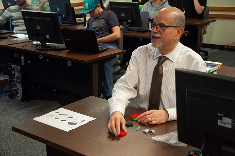 Director of Education, David Schaitkin, following LEGO instructions from Engineering students