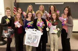 This photo shows a group of smiling females holding socks for the Sock It To Cancer fundraiser