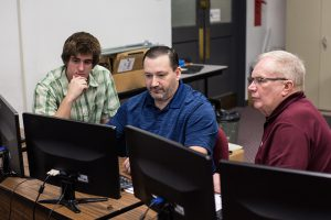 Three males working on a computer