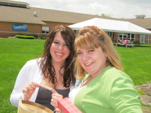 This photo shows two females smiling outside of the State College main campus