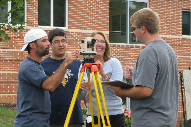Engineering Technology students smiling outside of the State College main campus while practicing surveying
