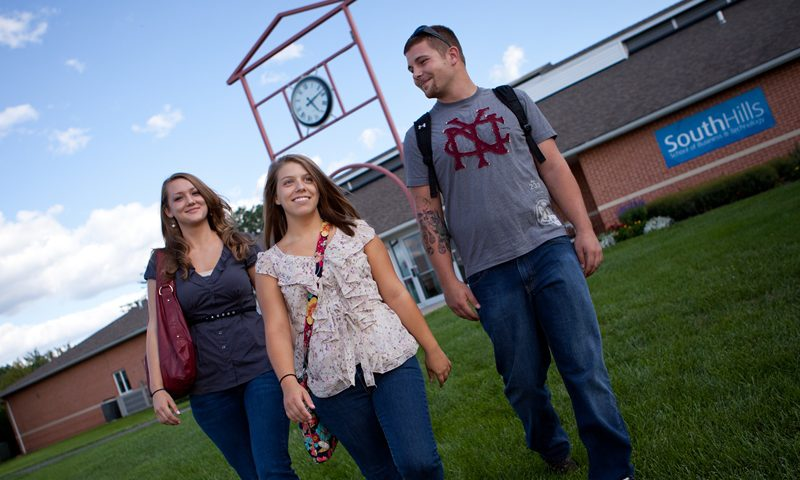 This photo shows students walking through the lawn at the State College campus