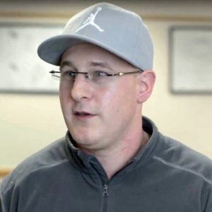 Male with glasses and baseball hat in classroom