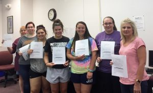 Medical Assistant students holding their EKG certification letters