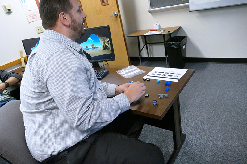 Information Technology Instructor, Matt Penning, assembling a LEGO car