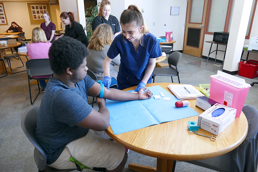Students of the Medical Assistant specialized associate degree program are shown practicing venipunctures.