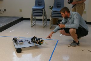 An Engineering Technology student with his robotic vehicle