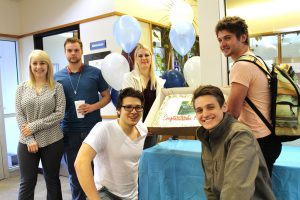 This photo shows smiling students holding a cake