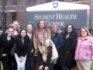 This photo shows a group of females smiling in front of the Student Health Center at Penn State