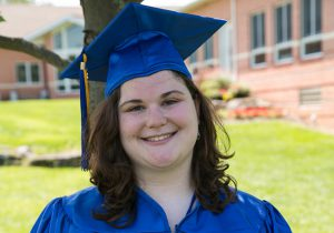 This photo shows a female graduate smiling outside of the Main Campus