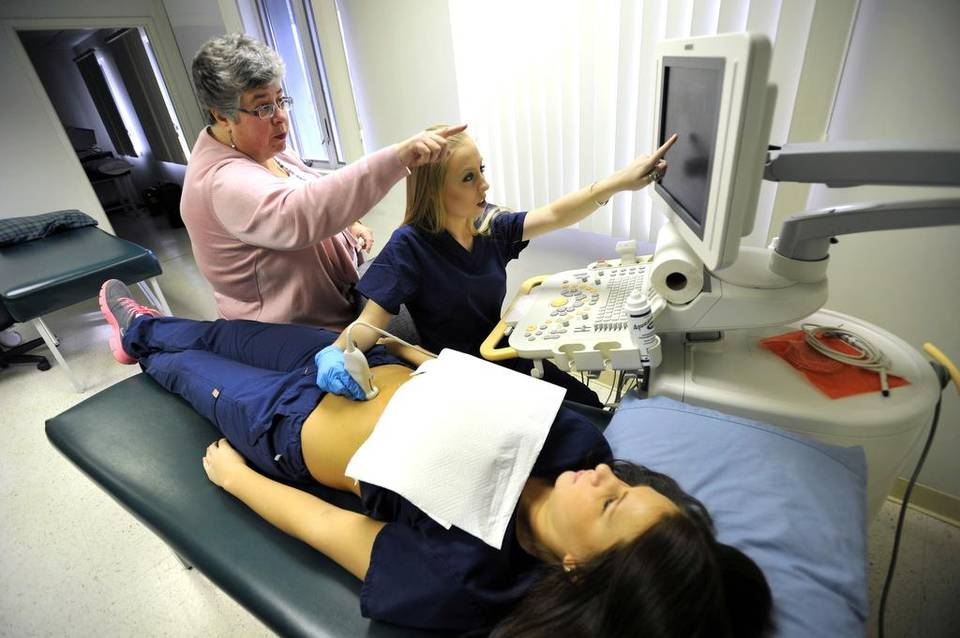 This photo shows sonography students practicing scanning in a medical lab