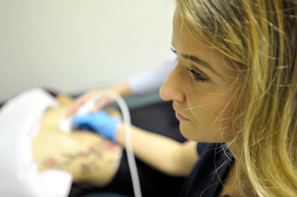 This photo shows a sonography student practicing scanning in a medical lab