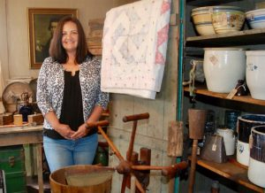 Female smiling standing next to antique items