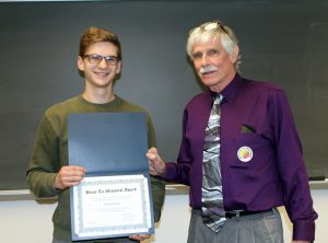 Male student smiling receiving award from instructor