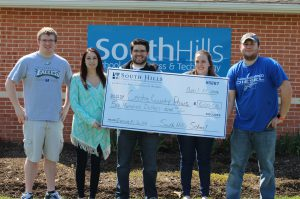 This photo shows South Hills students holding a large donation check outside of the main campus