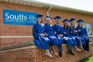 Graduates smiling outside of the State College Main Campus