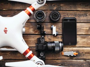 This photo shows a drone, a camera, and a cell phone