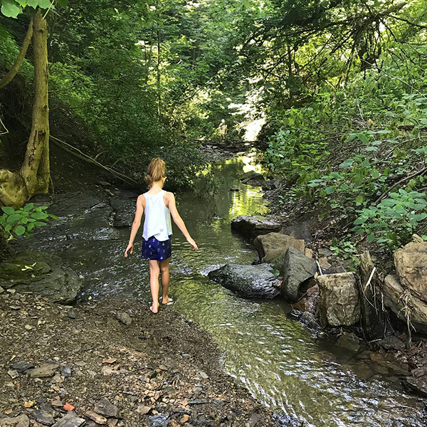 Jenny Charney's daughter walking by a stream in a forest