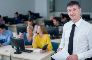 This photo shows a male in a classroom with students behind him on computers