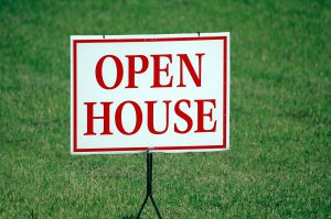 This is a photo of an Open House sign on a green lawn.
