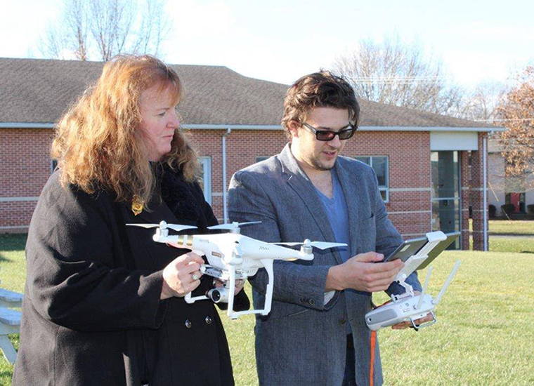 Two people operate a drone.